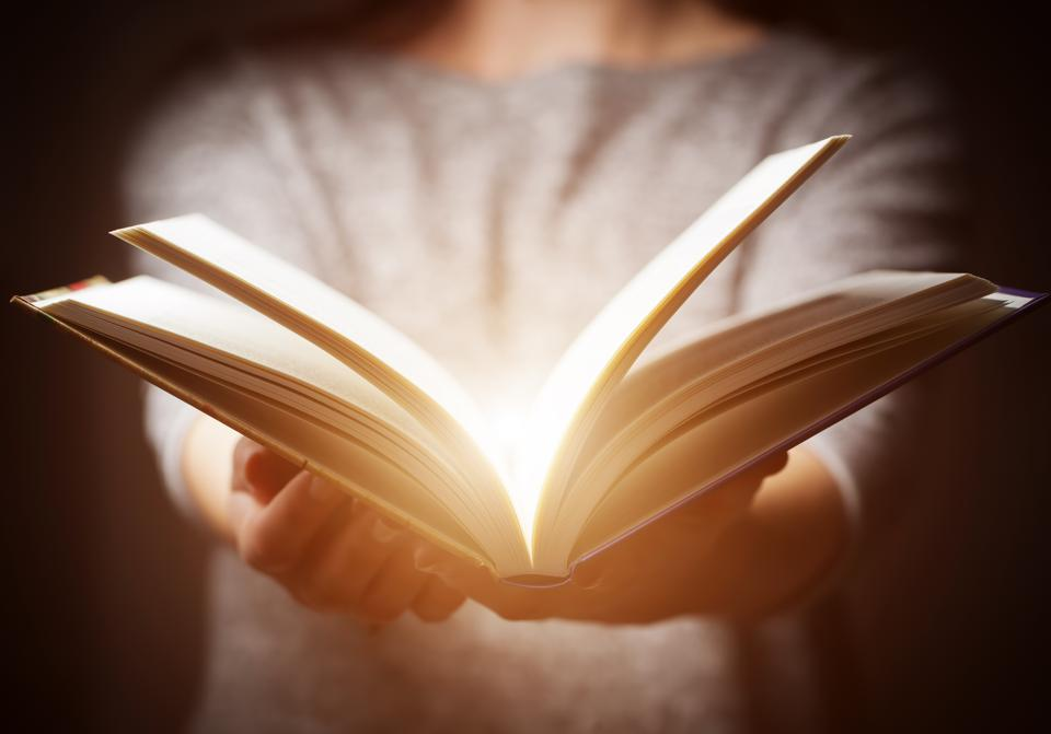 Light coming from book in woman's hands in gesture of giving