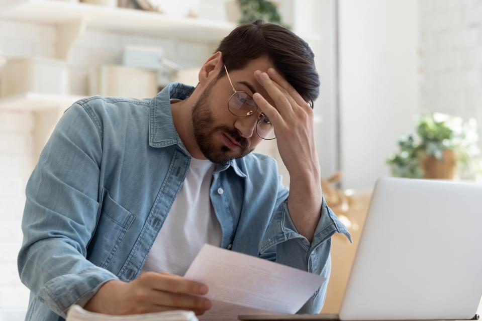 Upset frustrated young man holding reading postal mail letter