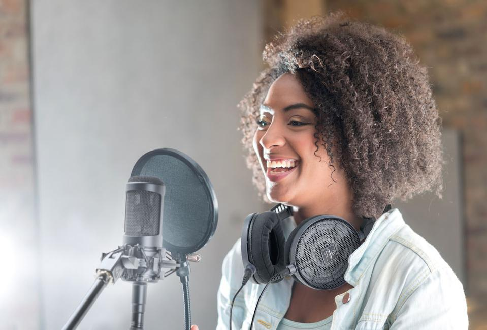 Young woman smiling behind AT2035 microphone at a recording studio
