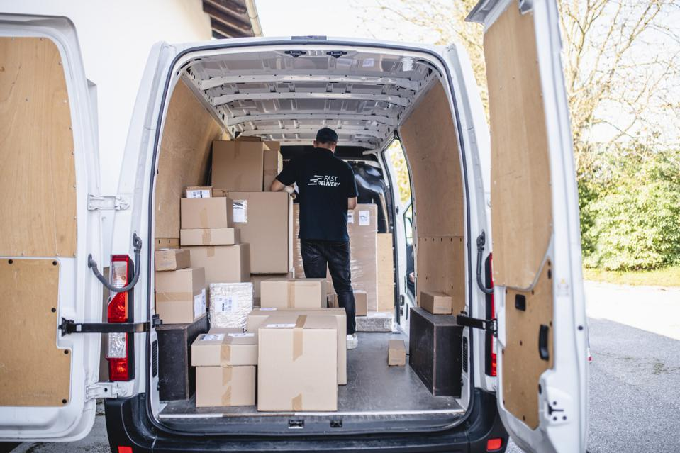 Independent Delivery Driver Organizing Parcels on Van