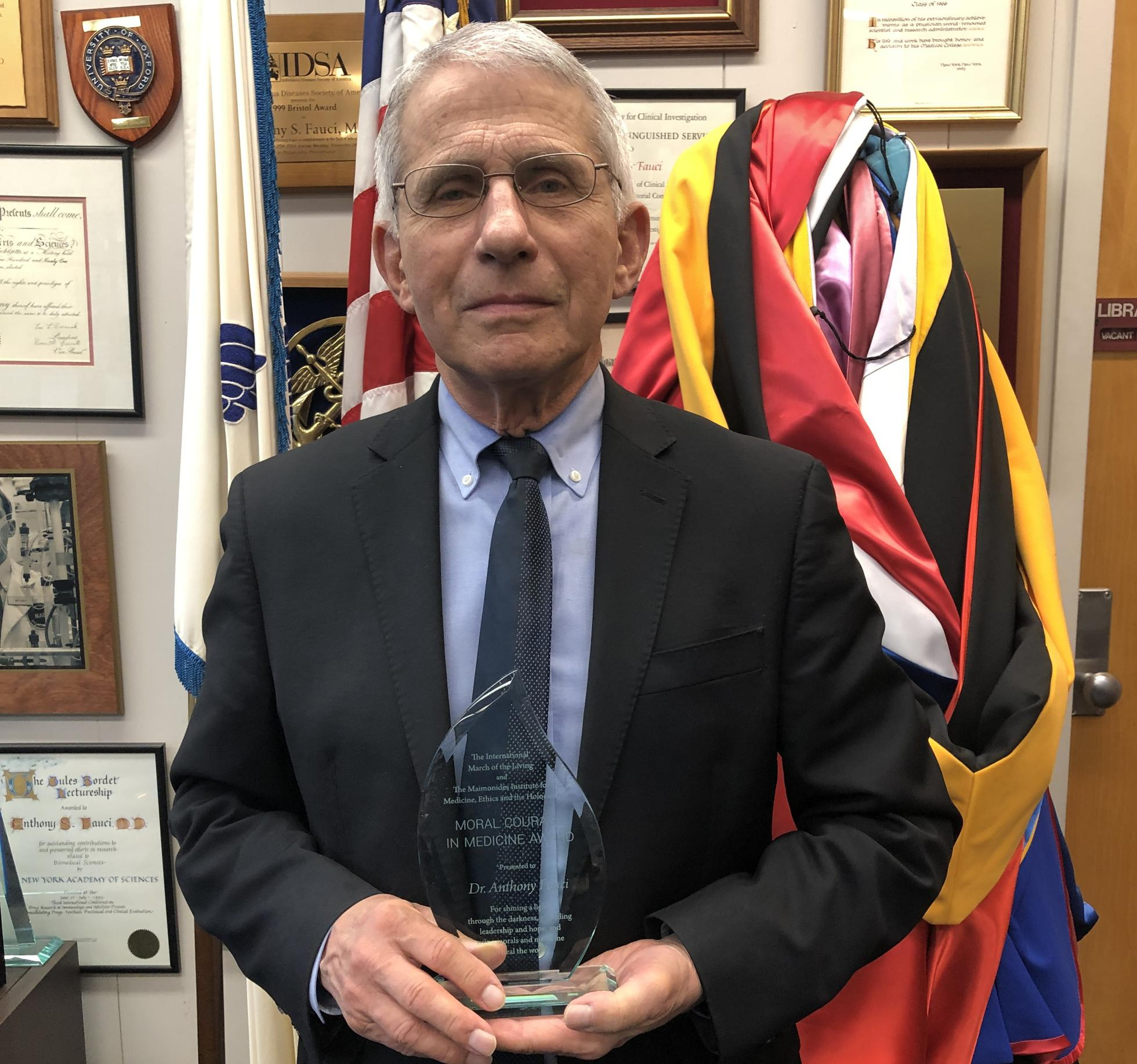 Dr. Facui holding the Moral Courage in Medicine Award.