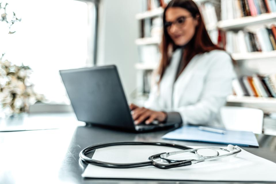 Doctor typing report on laptop