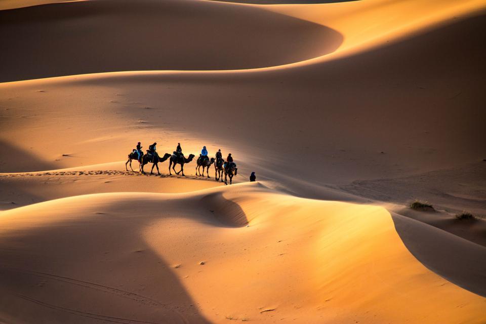 A,Caravan,Walking,Through,The,Golden,Sand,Dunes,Of,Erg