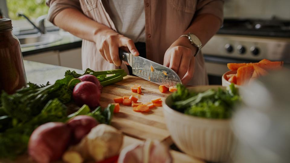 Closeup of young female hands chopping fresh vegetables on chopping board in kitchen