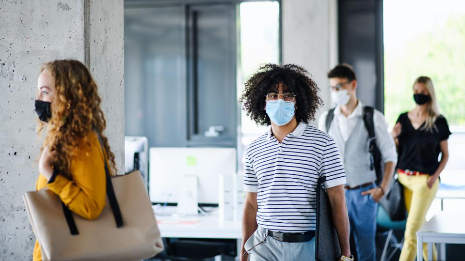 Young people with face masks back at work in office after lockdown, walking.