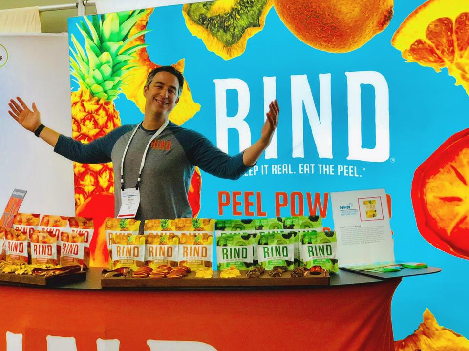 Weiss stands in front of a RIND banner with a table full of RIND snacks.