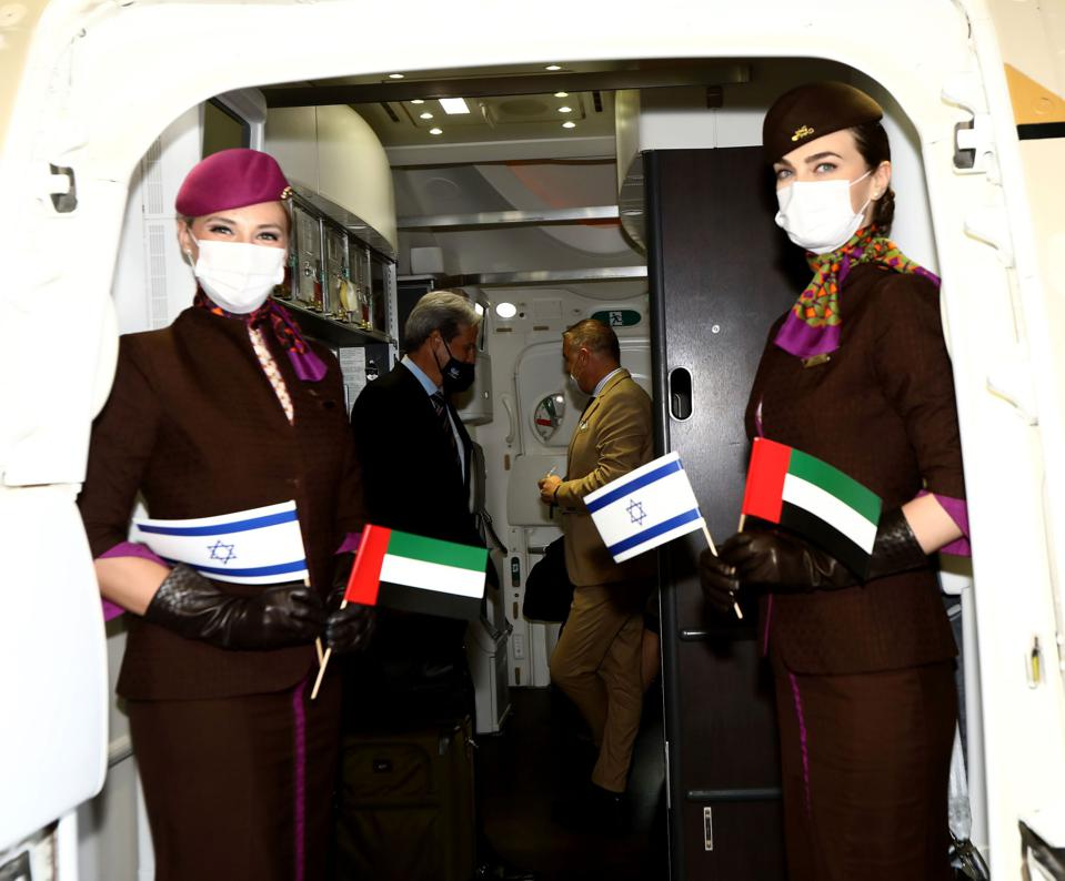 Flight attendants hold Israeli and Abu Dhabi flags.