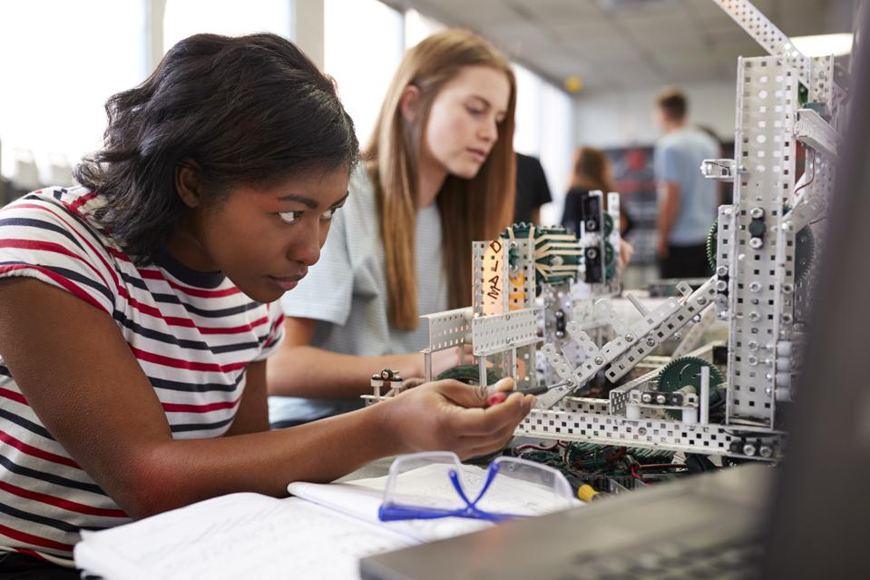 Two Female College Students Building Machine In Science Robotics Or Engineering Class