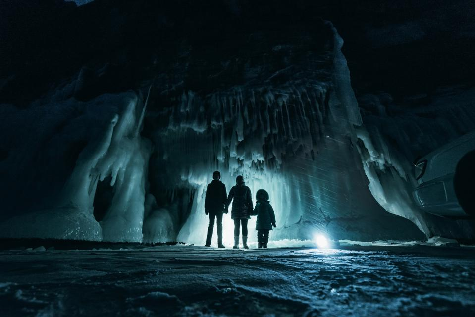 A family of three in a dark, ice filled grotto