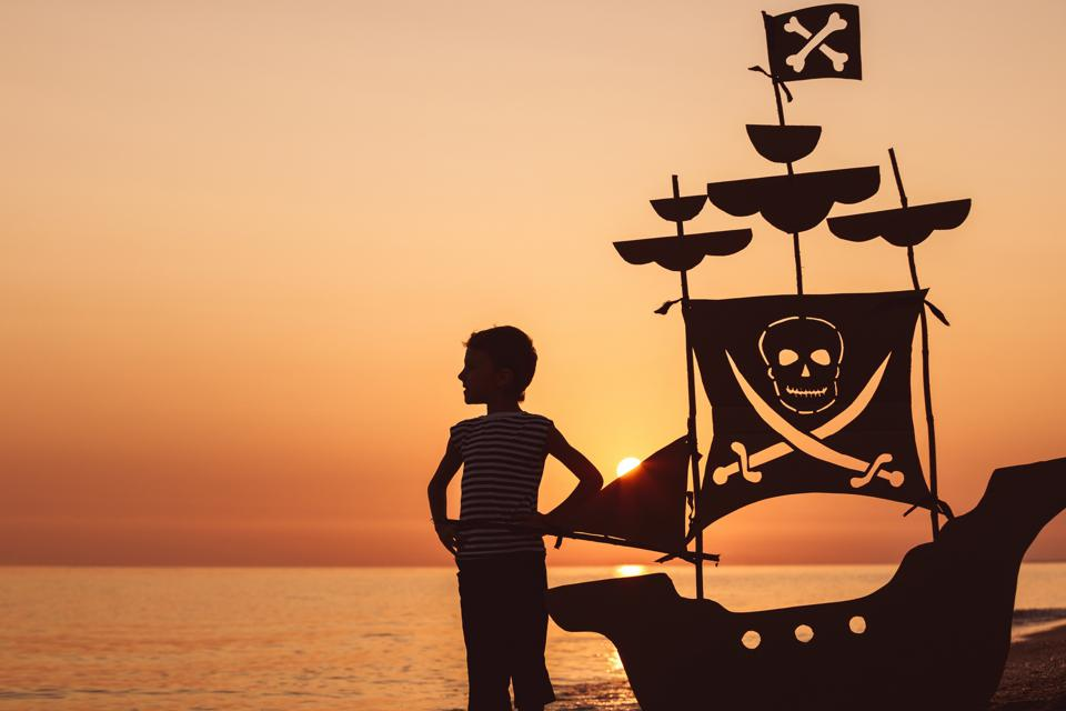 A little boy in silhouette at sunset with a pirate ship