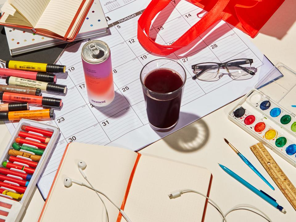 A glass of hibiscus Moment on a desk with paints, crayons, a notebook and calendar.