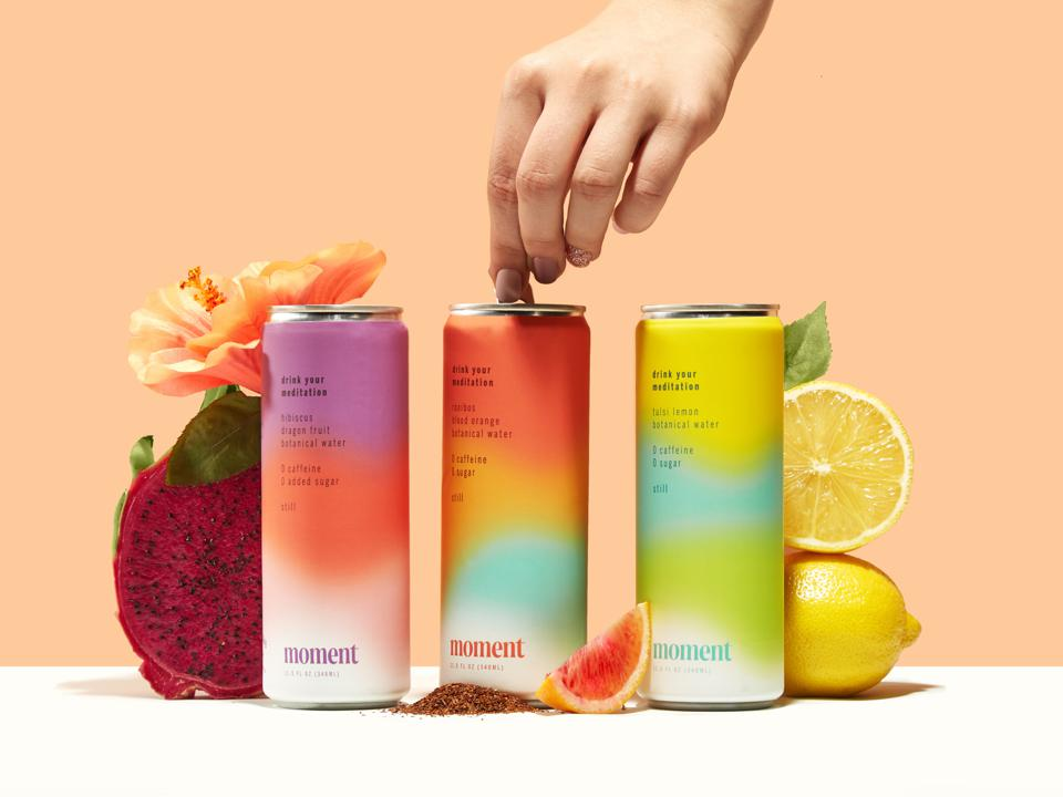 A hand opens a can of Moment meditation drink next to lemons and fruit.