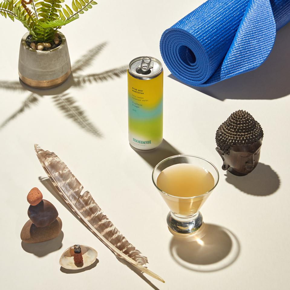 A can of lemon Moment displayed next to a yoga mat, feather and buddhist figure.