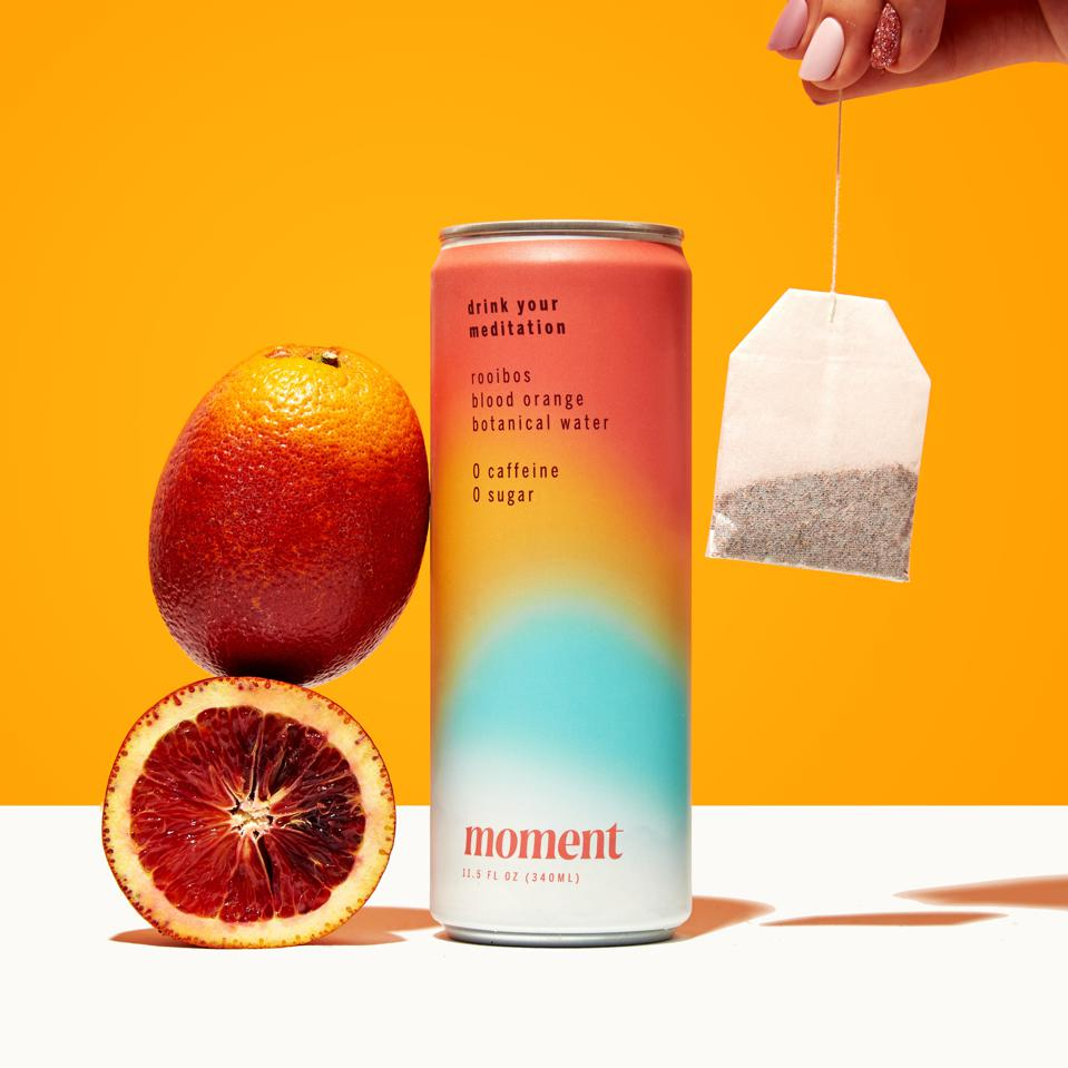 A can of roobios blood orange Moment next to a blood orange and a tea bag.
