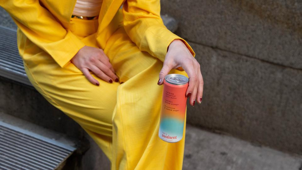 A woman in a bright yellow suit holds a can of Moment while sitting on concrete steps.