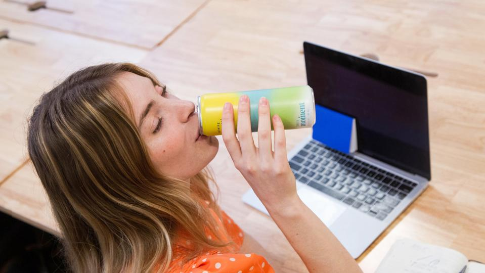 A woman drinks a can of Moment on her laptop.