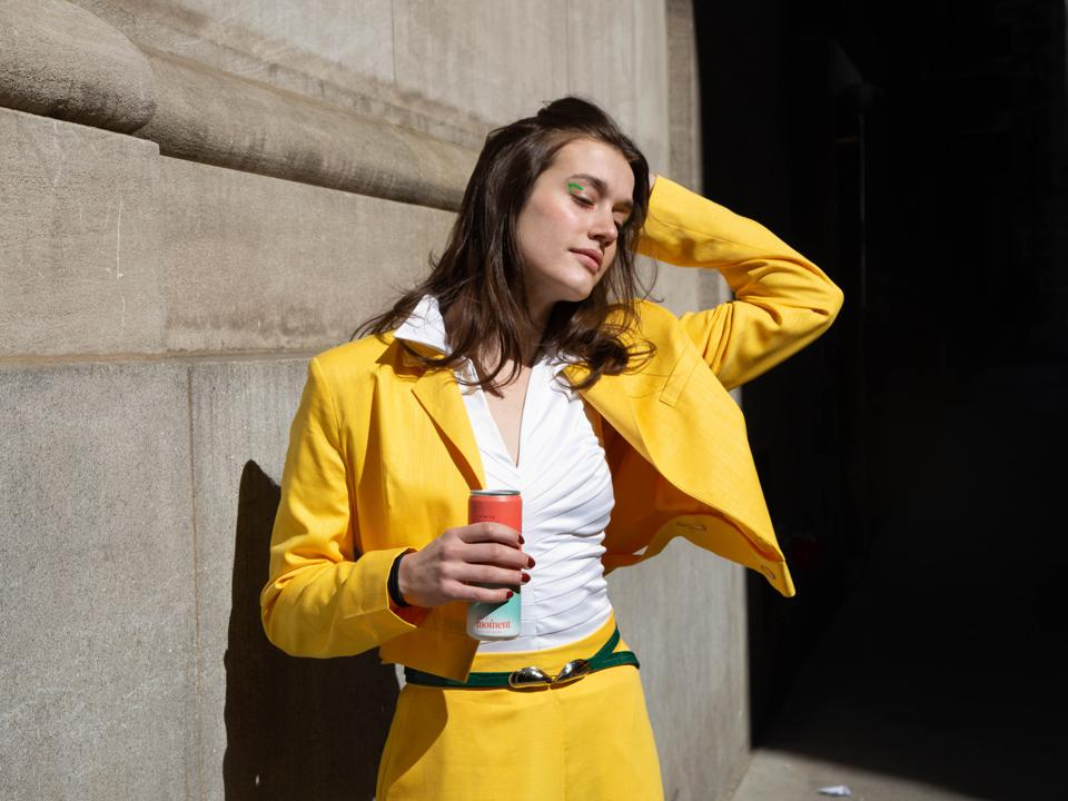 A woman in a bright yellow suit drinks a can of Moment while basking in the sun.