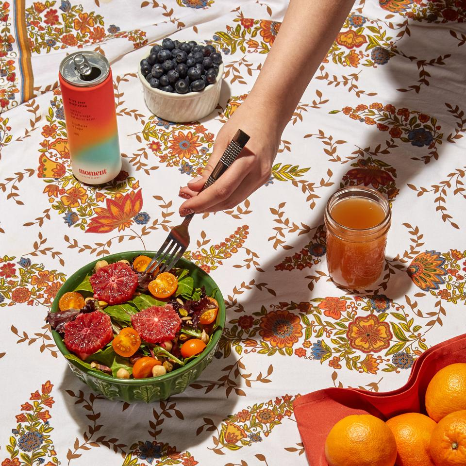 A hand picks up a fork from a salad bowl next to a box of Moment and fruit bowls.
