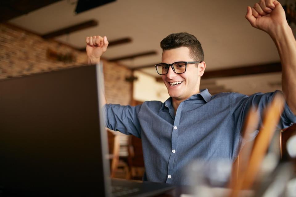 Handsome businessman with laptop having his arms with fists raised, celebrating success. Happy freelancer hipster in glasses finished work on project. Man won a lot of money in lottery prize