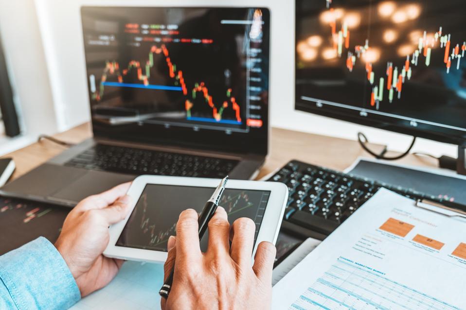 رجل أعمال يبحث في بيانات الأسهم على شاشات الكمبيوتر اللوحي والكمبيوتر