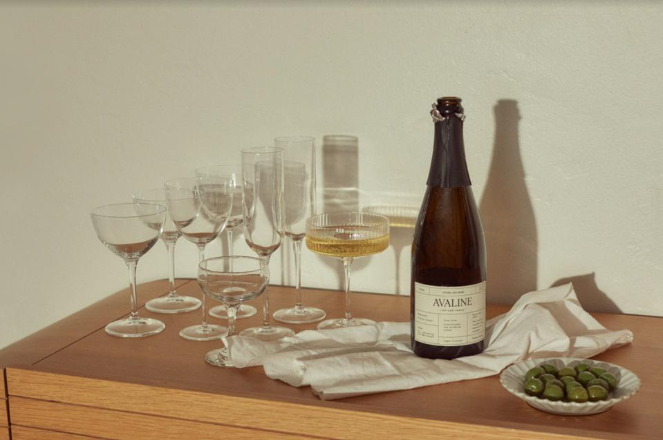 a bottle of sparkling wine next to assorted champagne coupes and glasses.