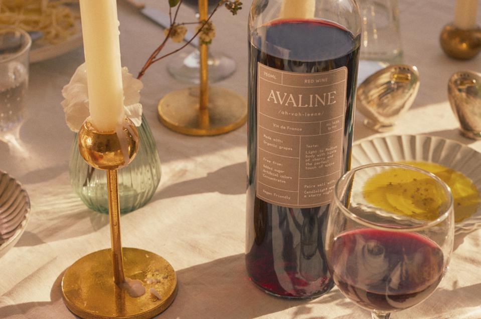 a bottle of red win with a candlestick and glass half full of wine.