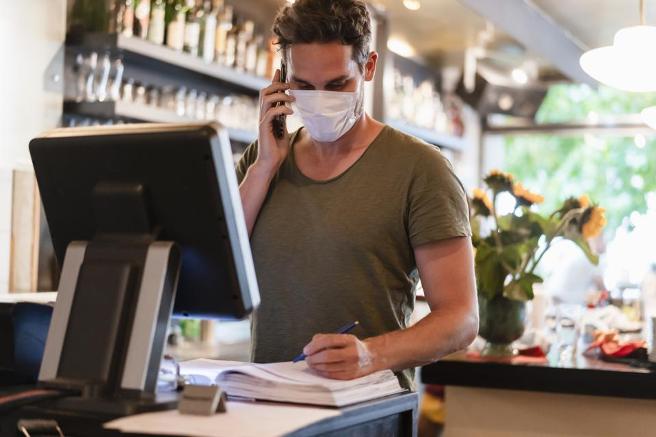 Restaurant manager with protective mask using computer and smartphone for reservation