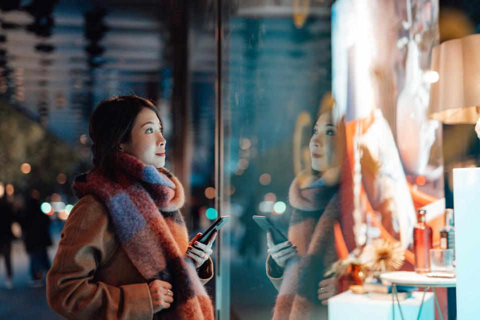 Young woman window shopping in the city at night