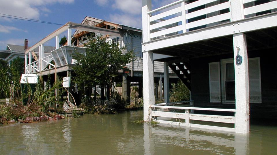 A row of houses on stilts that are heavily flooded.