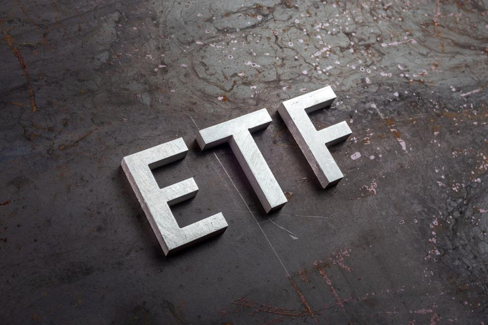the abbreviation word etf - Exchange Traded Fund - laid with silver letters on raw rusted steel sheet surface in slanted diagonal perspective