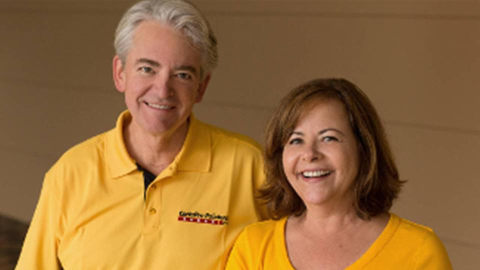 Eric and Pam Knauss owners of CertaPro franchise, smiling wearing yellow shirts.