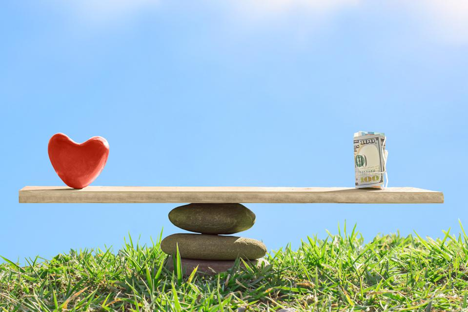 Red heart and dollar bills on the scales of stones showing the business case for happiness.