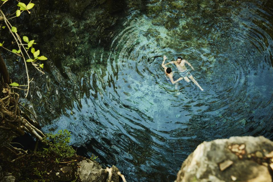 Overhead view of gay couple swimming in cenote while on vacation