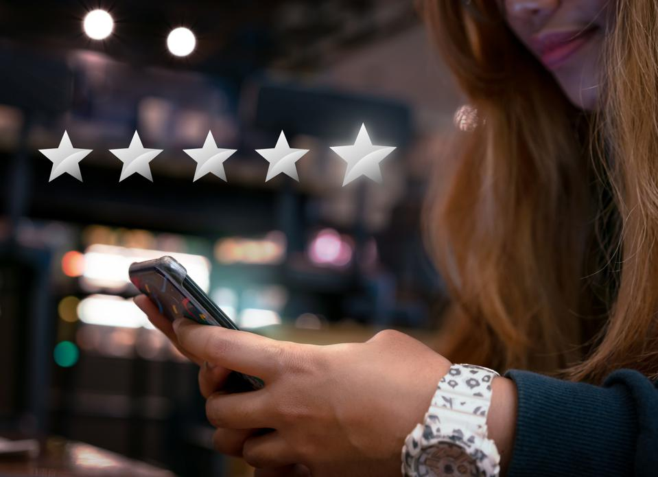 Hands of young woman submitting 5 star silver customer satisfaction feedback on mobile smartphone device to online shopping retailer