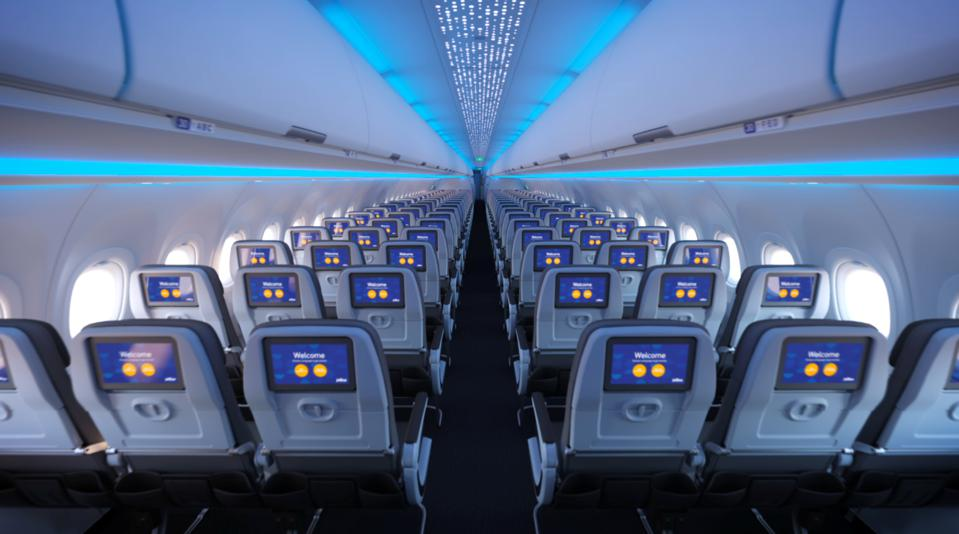 Forward view of aircraft coach cabin showing video screens on each seatback.