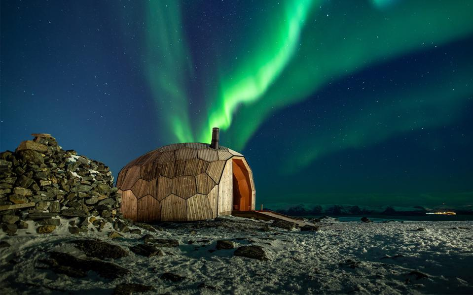 A northern lights display in the sky above a wooden cabin in Norway.
