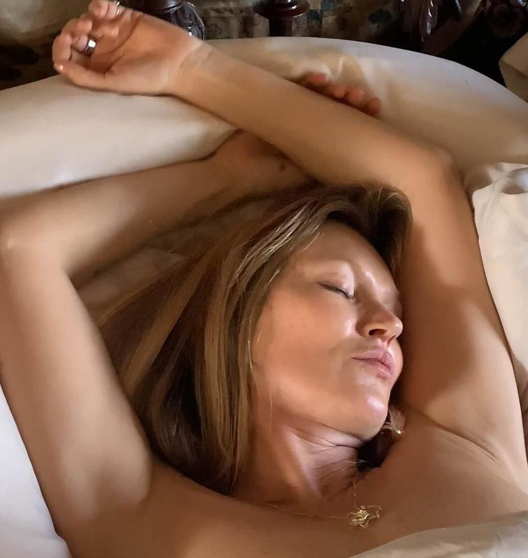 Kate Moss lying in bed with eyes closed and arms above her head