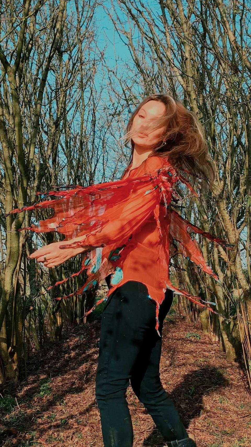 Kate Moss frolicking in a bohemian blouse in a tree lined path