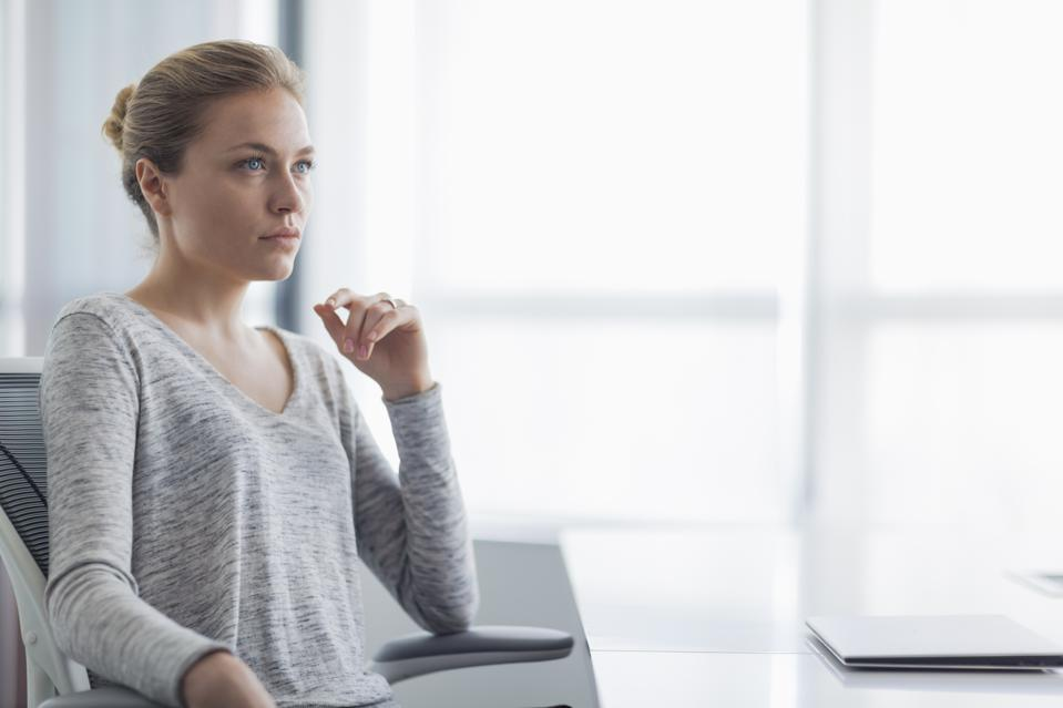 Young businesswoman listening speaker in office meeting