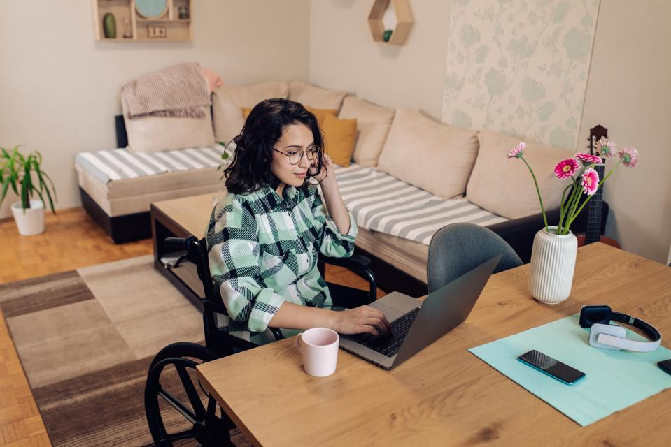 Young woman in a wheelchair freelancing from her home office