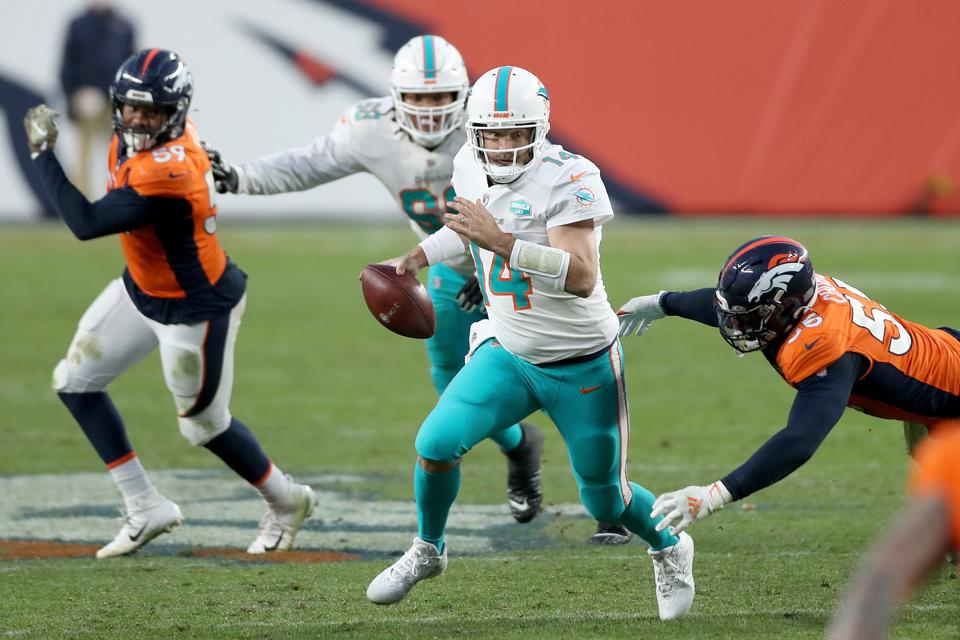 DENVER, COLORADO - NOVEMBER 22: Ryan Fitzpatrick #14 of the Miami Dolphins falls as he is tackled by Bradley Chubb #55 of the Denver Broncos during the fourth quarter at Empower Field At Mile High on November 22, 2020 in Denver, Colorado. (Photo by Matthew Stockman/Getty Images)