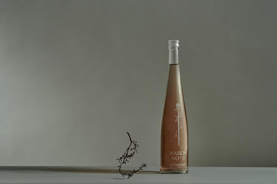 A bottle of rose sits next to a grape stem