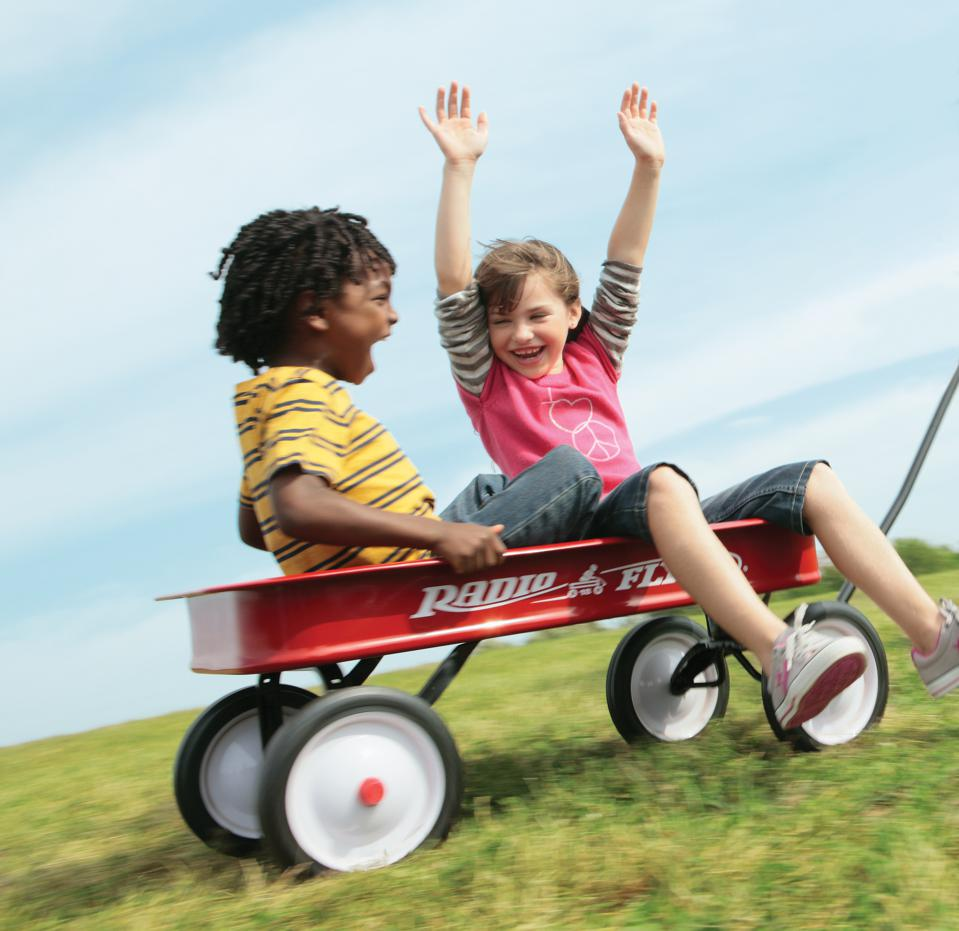 Two children having fun in red wagon showing importance of shared experiences.