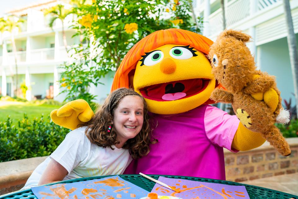 The Sesame Street character smiles for the camera with her arm around a smiling girl and with a stuffed animal in her other hand. Art projects are on the table in front of them.