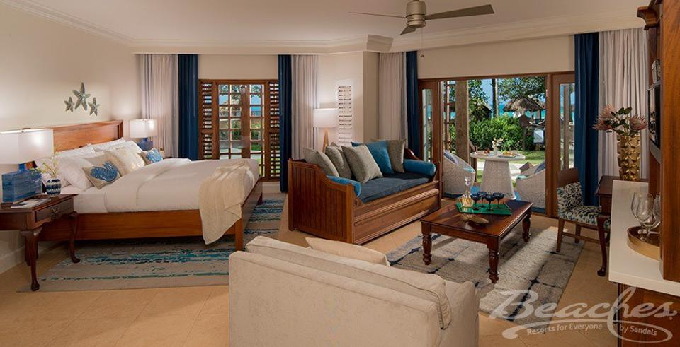 Part of a three-bedroom hotel suites with a king bed on the left an a living room on the right, looking out onto a sunny balcony.