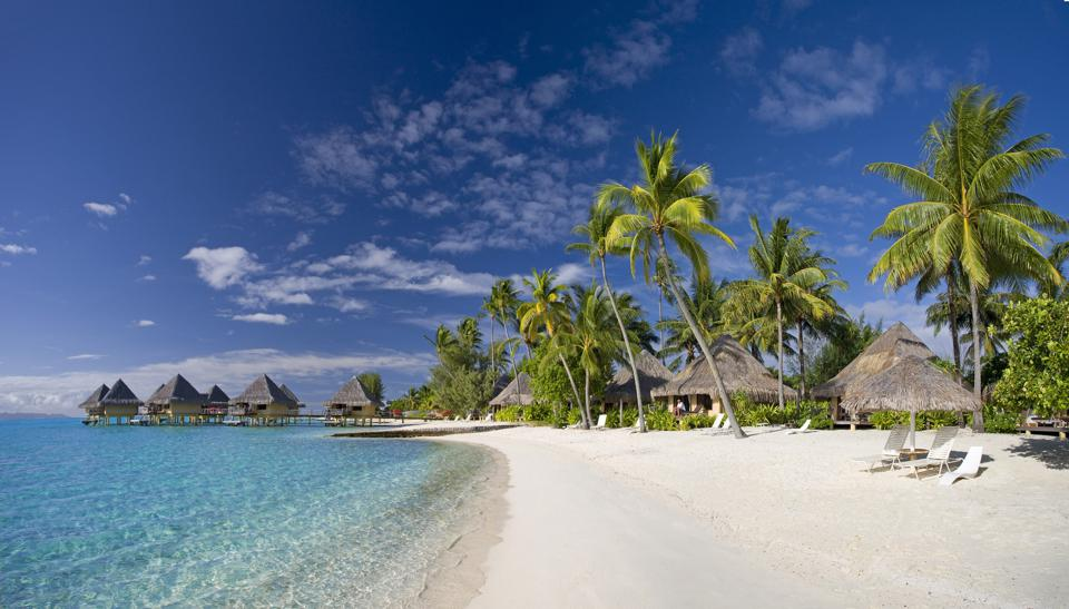 Tall thatch-roofed bungalows along the whote sand beach and over the ocean