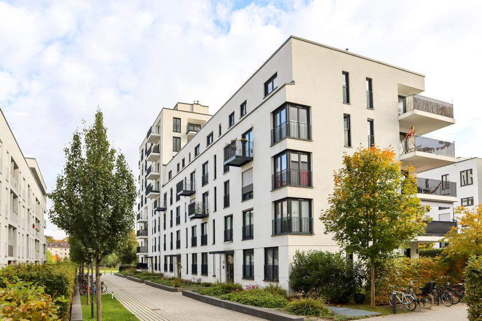 Paysage urbain avec quartier résidentiel moderne, nouveaux immeubles à appartements et cour verte avec trottoir et arbres en automne