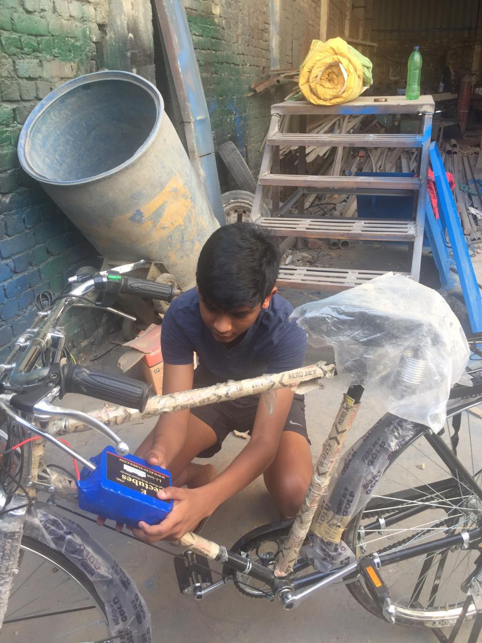 A high school student from India at the warehouse, working on a bicycle.