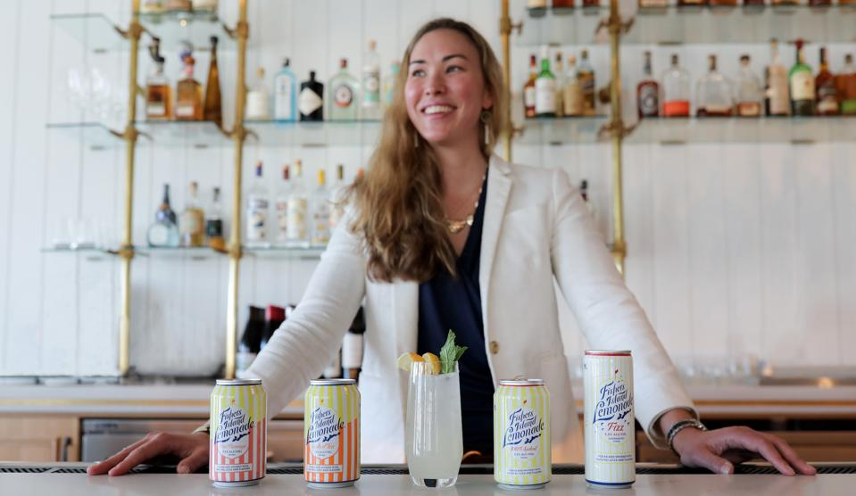 A woman in a white jacket stands behind a line of canned cocktails