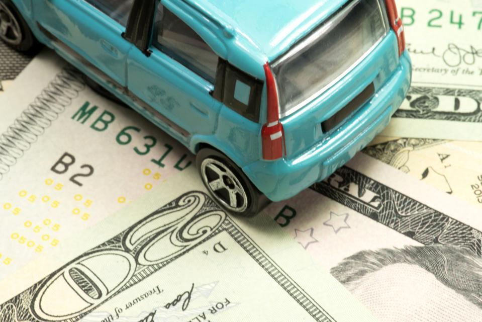A small car and dollar banknotes